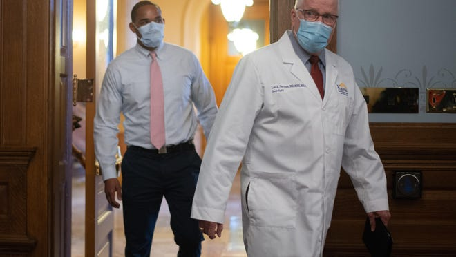 Lee Norman, right, Kansas secretary of health and environment, enters a news briefing Wednesday with Chris Brown, left, with the University of Kansas Medical Center, at the Kansas Statehouse.