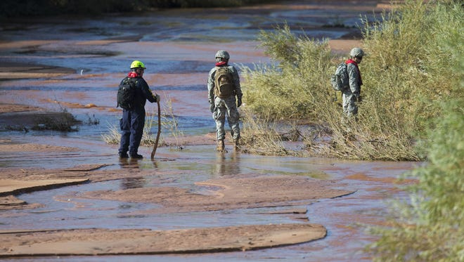 A search and rescue team look over Short Creek in Hildale, Utah on Sept. 16, 2015. Flash floods washed away multiple vehicles over a ravine, killing 12 people in Hildale, Utah on  Monday Sept. 14, 2015. Crews are still searching for a missing child.