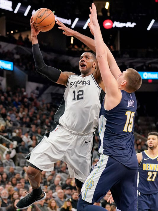 San Antonio Spurs' LaMarcus Aldridge (12) shoots against Denver Nuggets' Nikola Jokic during the second half of an NBA basketball game Tuesday, Jan. 30, 2018, in San Antonio. San Antonio won 106-104. (AP Photo/Darren Abate)