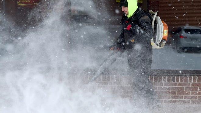 Robbie Martin with Stewart Property Maintenance, clears the sidewalk along the side of the Rutters during Saturday morning's early snowfall in West Manchester Township.