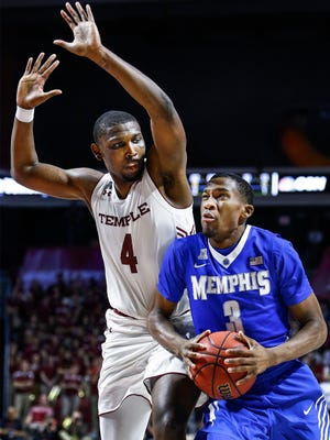 University of Memphis guard Jeremiah Martin (right) drives the lane against Temple University defender Daniel Dingle (left) during first action at the Liacouras Center in Philadelphia, Pennsylvania.