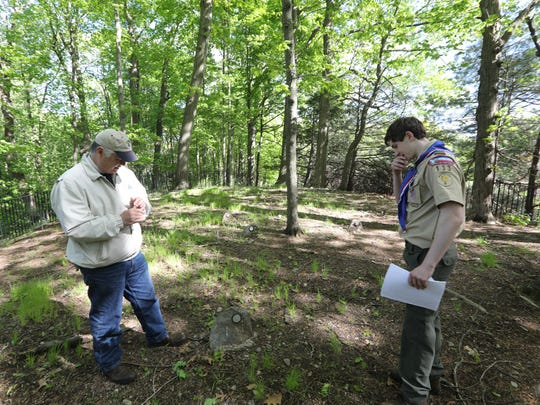 The Rev. Robert Fretz and Daniel Hynes are shown in the Old Stone Church cemetery on May 15. Fretz, pastor of the church, believes people who prayed at the church are buried in the cemetery. Hynes helped restore the cemetery for his Eagle Scout project.
