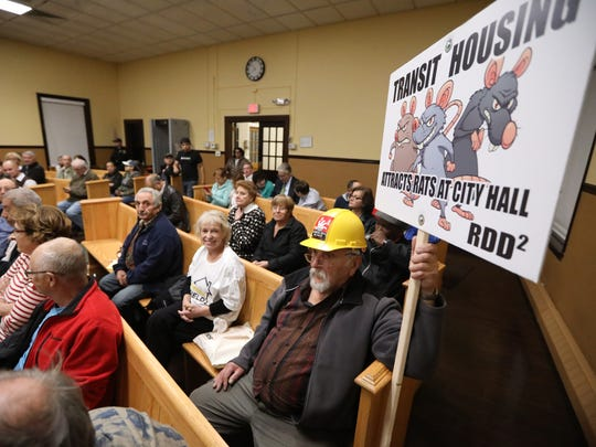 Mike Denistran, 72, holds a sign at an Oct. 26, 2017, public hearing for a study to determine whether 27 Garfield properties should be designated an area in need of redevelopment. Denistran has lived in Garfield for 65 years.