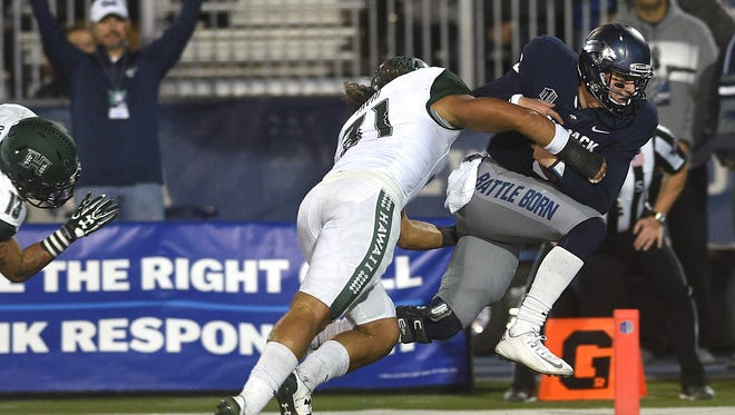 Nevada's Ty Gangi (6) rushes for a touchdown past Hawaii's Jahlani Tavai during their football game at Mackay Stadium on Saturday.