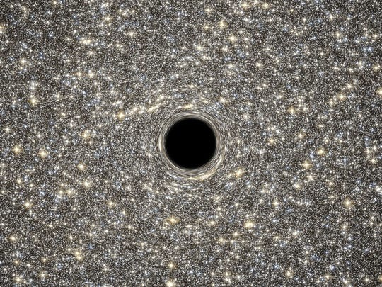 "A handout photo released on September 18, 2014 by ESA/Hubble shows an illustration of the supermassive black hole located in the middle of the very dense galaxy M60-UCD1. It weighs as much as 21 million times the mass of our Sun. Lying about 50 million light-years away, M60-UCD1 is a tiny galaxy with a diameter of 300 light-years  just 1/500th of the diameter of the Milky Way! Despite its size it is pretty crowded, containing some 140 million stars. Because no light can escape from the black hole, it appears simply in silhouette against the starry background. The black holes intense gravitational field warps the light of the background stars to form ring-like images just outside the dark edges of the black holes event horizon. Combined observations by the NASA/ESA Hubble Space Telescope and NASAs Gemini North telescope determined the presence of the black hole inside M60-UCD1.   AFP PHOTO / NASA/ESA/HUBBLE / D. Coe, G. Bacon (STScI)  = RESTRICTED TO EDITORIAL USE - MANDATORY CREDIT ""AFP PHOTO / NASA/ESA/HUBBLE / D. Coe, G. Bacon (STScI)"" - NO MARKETING NO ADVERTISING CAMPAIGNS - DISTRIBUTED AS A SERVICE TO CLIENTS =D. Coe, G. Bacon (STScI)/AFP/Getty Images ORIG FILE ID: 533519444"
