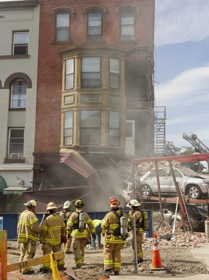 Ithaca firefighters work in front of Simeon's on June 20, 2014, after a tractor-trailer loaded with vehicles crashed into the restaurant at the east end of The Commons.