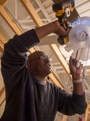Alexis Robinson tightens screws in a fan that he learned to install in a practice model frame for a residence at the Franklin County Career and Tech Center on Wednesday, Feb. 10, 2016.  Robinson wants to take back what he learned and open a professional school in Haiti.
