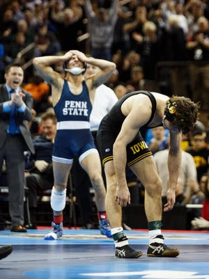 Iowa's Thomas Gilman is discouraged as Penn State's Nico Megaludis celebrates his 125-pound NCAA title after a 6-3 victory at Madison Square Garden. Iowa went 0-3 in championship bouts.