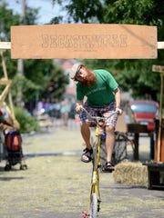 David Charles Murphy rides his tall bicycle underneath