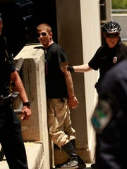 A Knoxville Police officer arrests protester Kynan