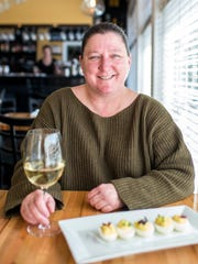 Traci Taylor, of Fig in Biltmore Village, sits with her favorite menu item, deviled eggs, at the bistro.