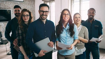 Group of smiling people standing in a room. One is holding a laptop, while others are holding paper.
