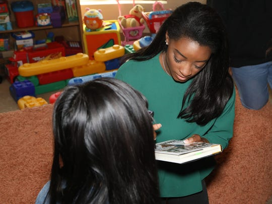 After speaking to abused children being treated at the Sinatra Center, Biles signed autographs in her book 'Courage To Soar.'