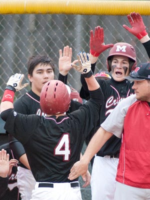 Manual Crimsons' Riley Noe gets high fives from his teammates after scoring on a wild pitch in the 3rd inning. Noe had doubled and moved to 3rd on a ground out, putting him in scoring position.30 March, 2016