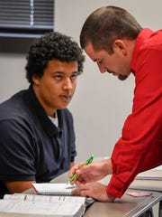 Academy for Innovative Studies teacher David Steckel helps Jamaal Wilson with a class problem in geometry class.