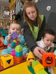 Emily Brink, an infant's teacher at KinderWorld, plays with Laila Sjodin, left, and Myah Thurman, right, as the children play Tuesday Dec. 20, 2016.