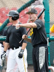 Iowa Hawkeyes head coach Rick Heller hits ground balls