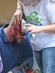 A medical volunteer treats an injured demonstrator