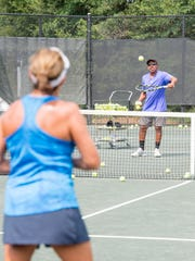 Instructor Linsley McMillion, right, hits a ball to Tomi Tyson during a lesson Sept. 5, 2017, at the Roger Scott Tennis Center in Pensacola.
