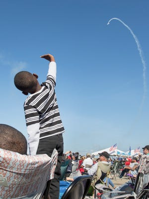 Freddrick Hunt, 5, of Jackson, Alabama, mimics the flight of a vintage plane Saturday, Nov. 11, 2017, during the Blue Angels Homecoming Air Show at Pensacola Naval Air Station.