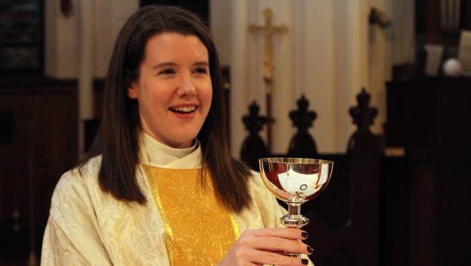 The Rev. Meghan Holland at the altar at Trinity Episcopal Church in Clarksville, Tenn.
