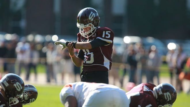 Scarsdale quarterback Michael Rolfe checks his wristband during a playoff game against Mamaroneck.