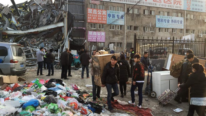 Residents carrying their belongings evacuate the site of a fatal housing block fire in Beijing on Nov. 19, 2017.