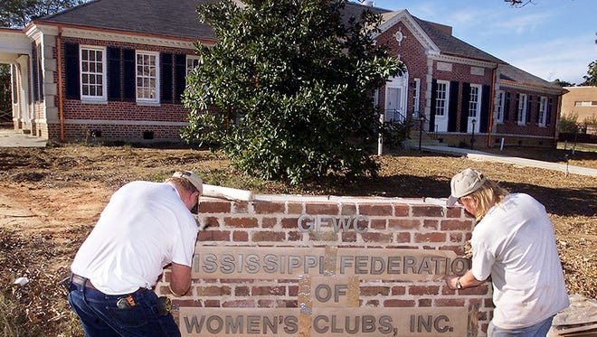 This file construction workers attaching lettering to a sign outside the Mississippi Federation of Women's Clubs building.