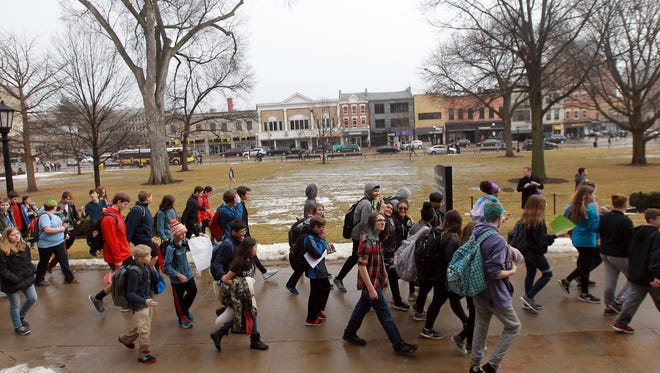 High school and junior high students march to the pedestrian mall following a walk-out on Monday, Feb. 19, 2018. Students from around the school district gathered at the Pentacrest and pedestrian mall to protest gun violence following the shooting at Marjory Stoneman Douglas High School in Parkland, Fla.