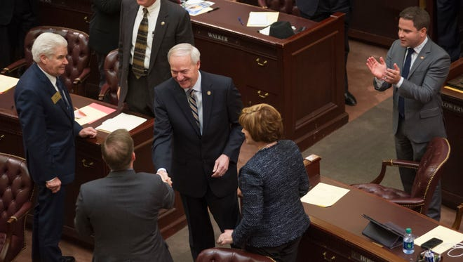 """In this Tuesday, Jan. 10, 2017, photo, Arkansas Gov. Asa Hutchinson, center, greets legislators before his address to a joint session 91st General Assembly at the state Capitol in Little Rock, Ark. President-elect Donald Trump and congressional Republicans have pledged to cut federal taxes to boost the economy. But some GOP-controlled states have already adopted similar strategies, only to see growth falter and budget gaps widen. """"It does not take a Ph.D. in economics to know that we can't say yes to every spending need, and we should also not say yes to every tax-cut idea,"""" Hutchinson warned late last year."""