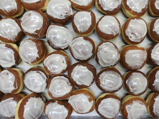 After each paczki cools, it is sprinkled with powdered