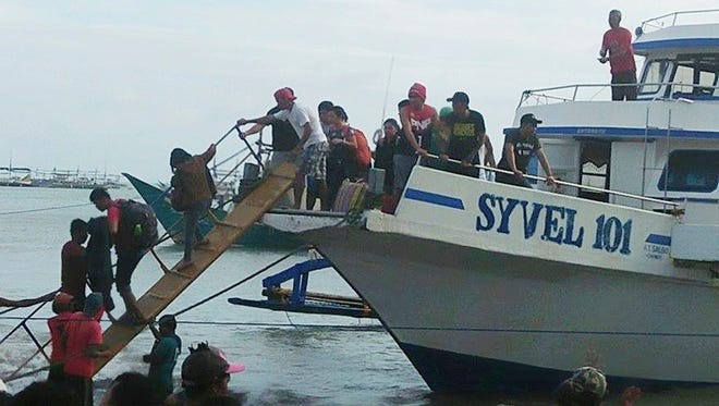 Rescued passengers from the ill-fated M/V Mercraft 3 disembark from a boat which helped in the rescue operation at Infanta township, Quezon province in northeastern Philippines on Dec. 21, 2017.