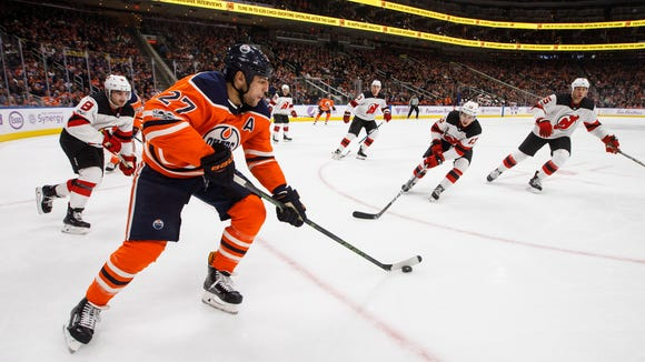 New Jersey Devils give chase as Edmonton Oilers' Milan Lucic (27) controls the puck during second-period NHL hockey game action in Edmonton, Alberta, Friday, Nov. 3, 2017. (Jason Franson/The Canadian Press via AP)