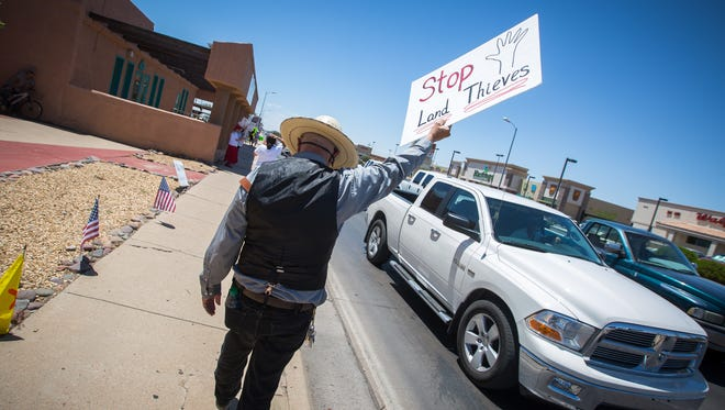 Jeff Swanson raises a sign as part of a protest in Alamogordo, July 9, 2016, opposing the Stand By Me for Liberty group which was holding a rally across the street at Alameda Park. Stand by Me for Liberty says that the New Mexico Bureau of Land Management and the U.S. Forest Service is violating rancher's private property and water rights.