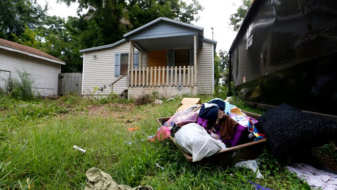 A dumpster sits in the yard of an abandoned house with trash scattered around the yard. Houses like this have become dumping grounds and are considered chronic nuisance properties by the city.