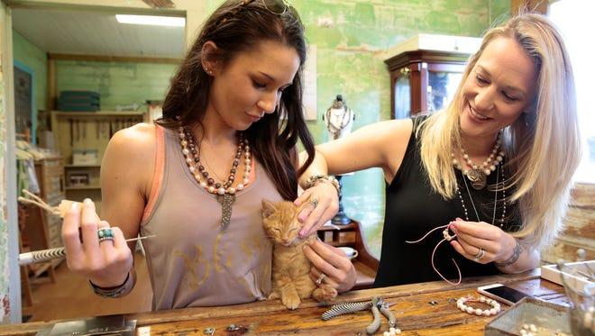 Lauren Landry and Ashley Leget pet Lauren's kitten at the Blessed Mess workshop in Breaux Bridge May 4, 2016.