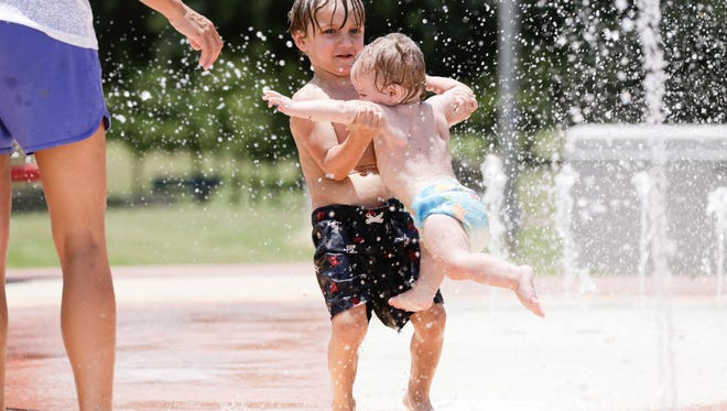 Zayden James plays with his little brother Zavier in the water pad at Girard Park July 9, 2016.