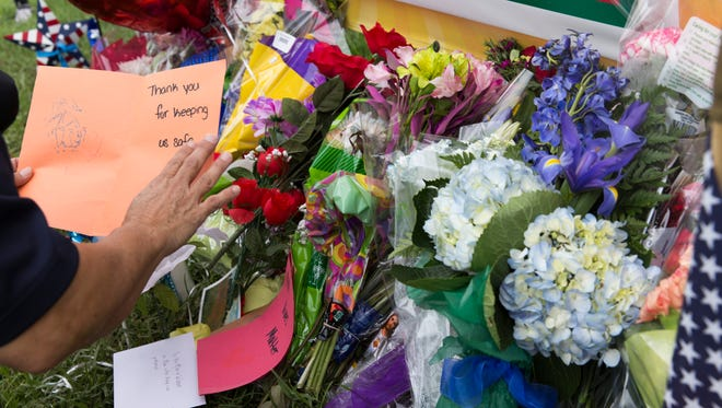 Retired Baton Rouge police sergeant Linda Giordano leaves a note at a makeshift memorial July 18, 2016 at the site of a shooting that left three policemen killed and three wounded in Baton Rouge July 17.