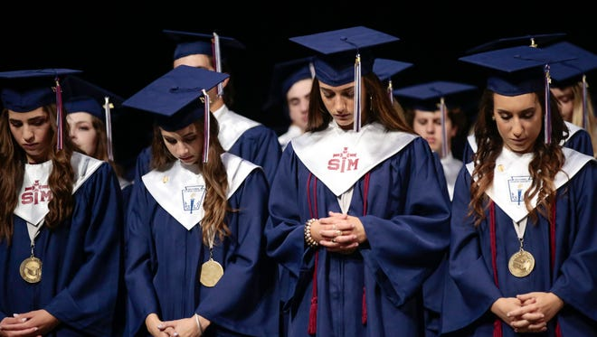 Graduates bow their heads in prayer during the benediction at St. Thomas More's graduation at the Cajundome Monday, May 16, 2017.