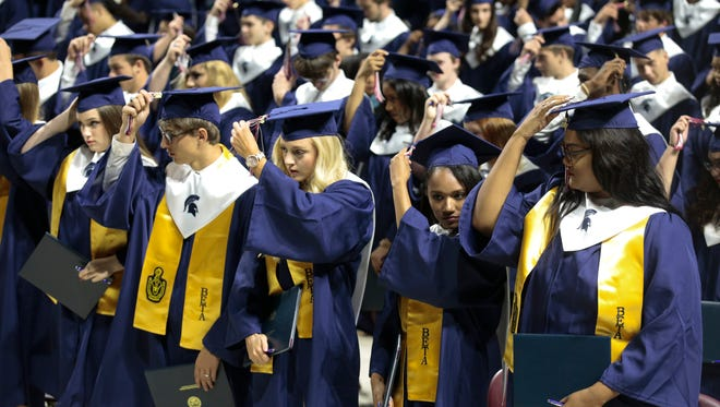 Graduates turn their tassels from right to left, to symbolize their graduation from high school, during the commencement of Comeaux High at the Cajundome Sat., May 20, 2016.