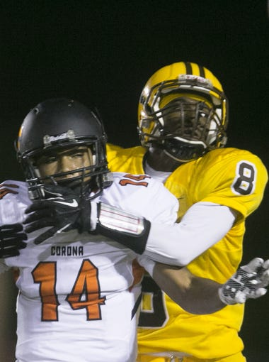 Corona del Sol's Kobee Marion (14) and Marcos de Niza's Montre Williams (8) attempt to catch a ball in the end zone at Marcos de Niza High School in Tempe, AZ on October 23, 2015.