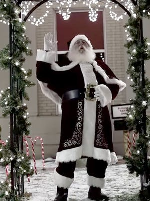 """Santa Claus waves after collecting 323 letters from area children, who deposited their wish lists and requests in special """"North Pole Express"""" box in front of the Sturgis police and fire department building."""