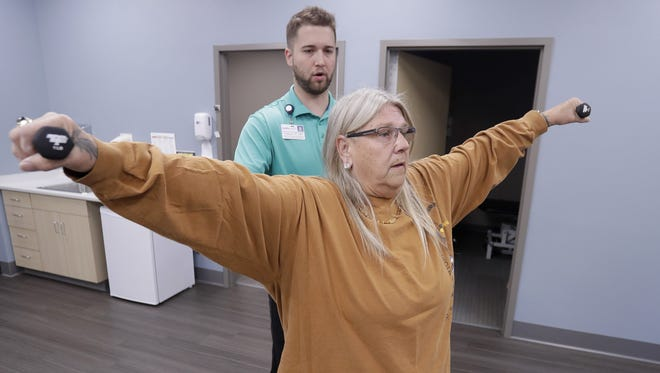 Bellin Health physical therapist Phillip Birdsall works with Jill Kirchner, a truck driver for America's Service Line, during a physical therapy evaluation at the new American Foods Clinic on Thursday in Green Bay.