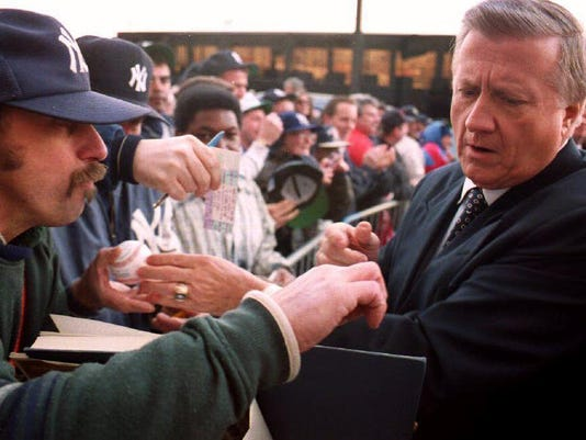 George M. Steinbrenner signs autographs as he ente