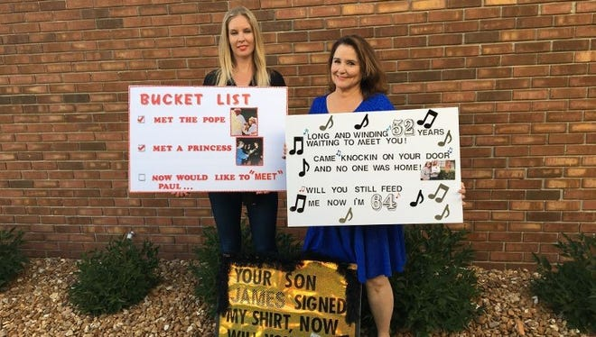 Christine Wofford (right) of Canton and her daughter Olivia with the posters they took to the Paul McCartney concert.
