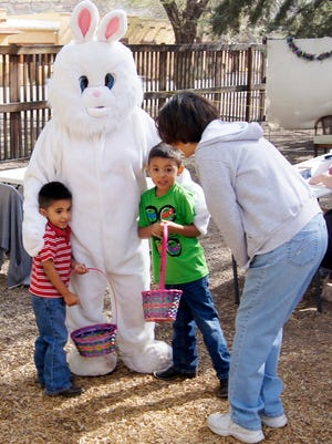 The Easter Bunny gives out hugs to two young egg hunters during last year's Kiwanis Easter Egg Hunt at Penny Park in Silver City.