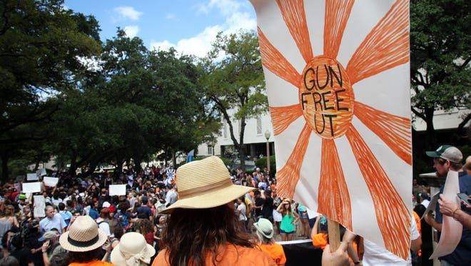 """A protestor carries a sign calling for a """"Gun Free UT"""" as he joins others during a protest on campus in Austin, Texas, on Aug. 24."""