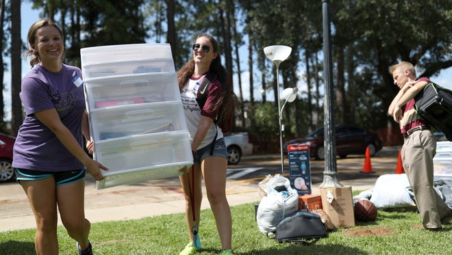 Moira Conley, left, and Jessica Meyer of the Honors Student Association, help incoming students as they move in to the FSU residence halls on the university's campus on Wednesday, Aug. 23, 2017.