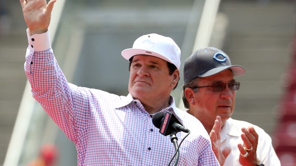 Former Reds great Pete Rose waves to the crowd as former teammate Johnny Bench applauds during Sunday's ceremony to retire Rose's number 14.