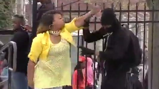In an image taken from video, a woman later identified as Toya Graham wrangles her son after she found out that he was rioting in Baltimore on Monday.